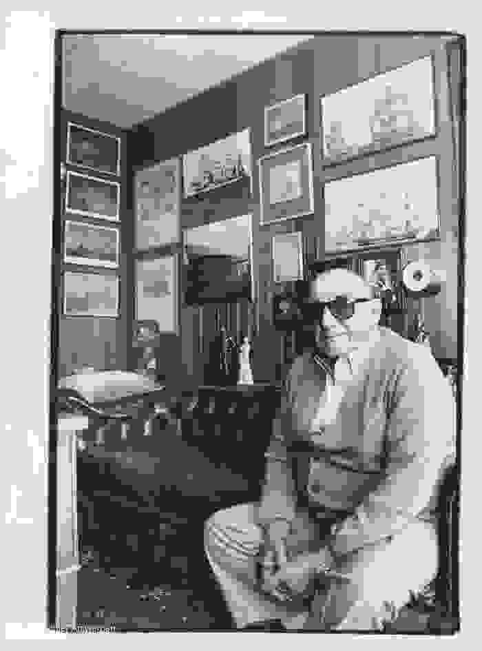 Eugène Colson sur un divan devant un mur couvert de cadres