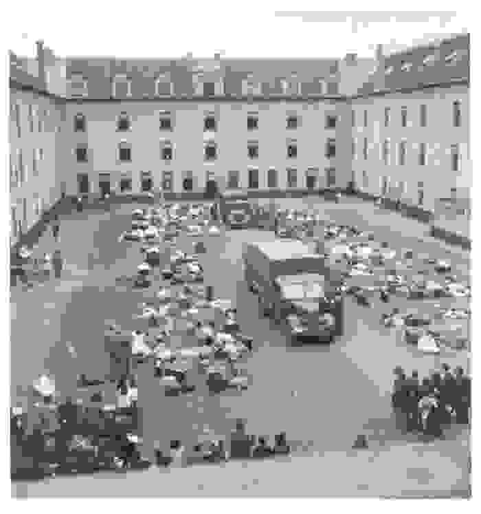 Des biens personnels jonchent la cour intérieure de la Caserne Dossin, avec au milieu un camion stationné